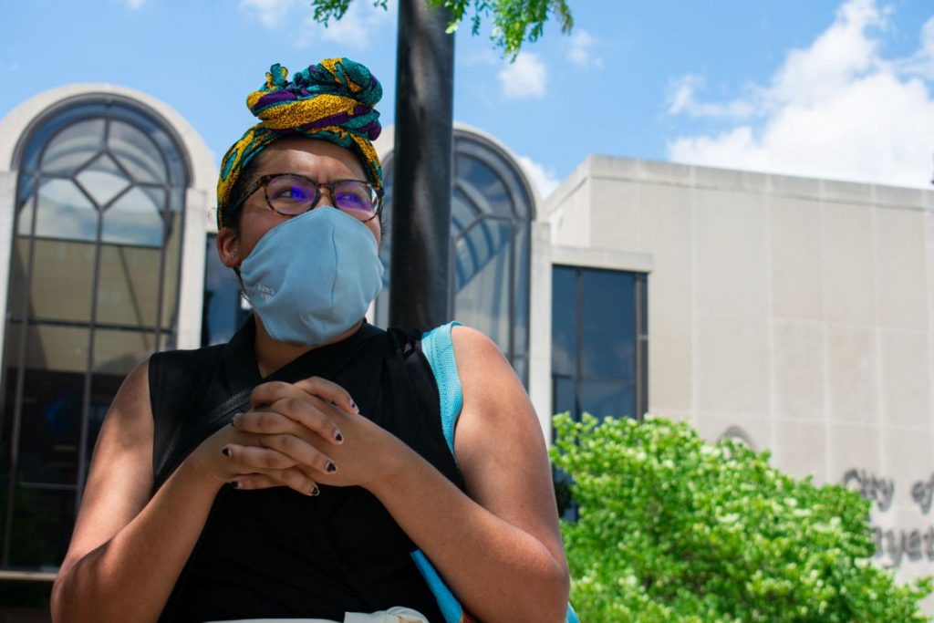photo of a Black woman wearing a headwrap, standing in front of Lafayette City Hall