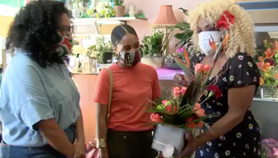 three Black women wearing face masks talk in a flower shop