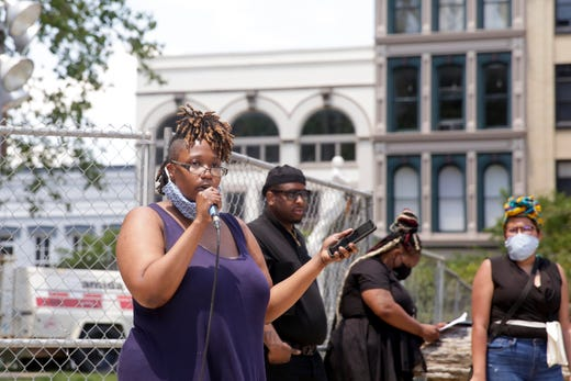 Black woman addesses a crowd using a microphone